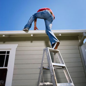person stepping off of latter onto a roof